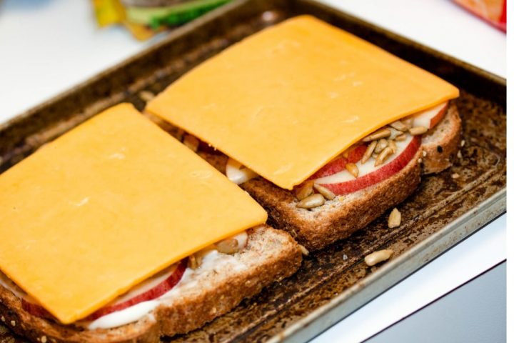 Open-faced Apple Cheddar Melt Sandwich with bread, mayo, apple slices, sunflower seeds, and cheddar and text Add Salt & Serve