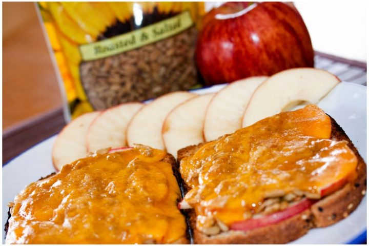 Open-faced Apple Cheddar Melt Sandwich with bread, mayo, apple slices, sunflower seeds, and cheddar melted on top and text Apple Cheddar Melt: Add Salt & Serve